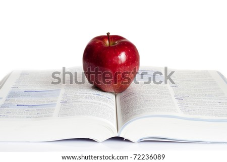 Red  apple placed on the top of the  book.