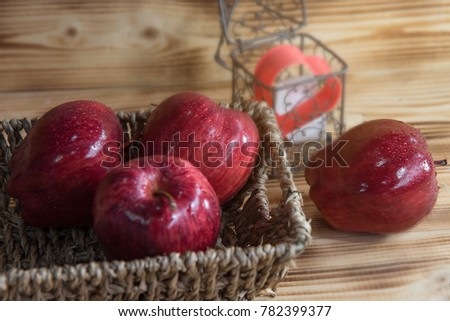 Red apple put in the basket. Located on a wooden desk. Near cartoon heart in wire box. #782399377