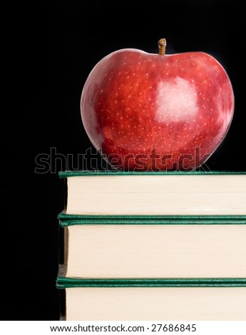 Red apple red on a green book on a black background