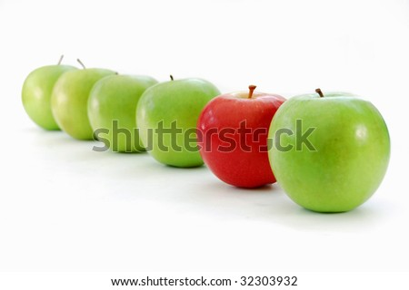 Red apple stands out in a line of green apples