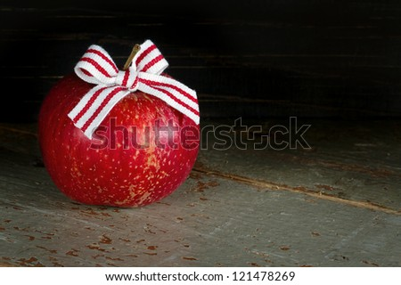 Red apple with Christmas bow on dark wooden rustic background