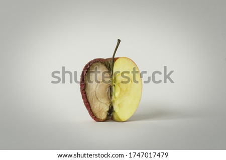 red apple with one half good and the other half rotten, concept of time, fruit that becomes garbage and that is thrown away, white background, isolated object Foto stock ©