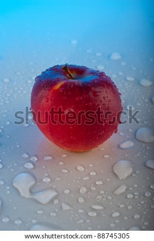 Red apple with water drops on gray table   with blue light