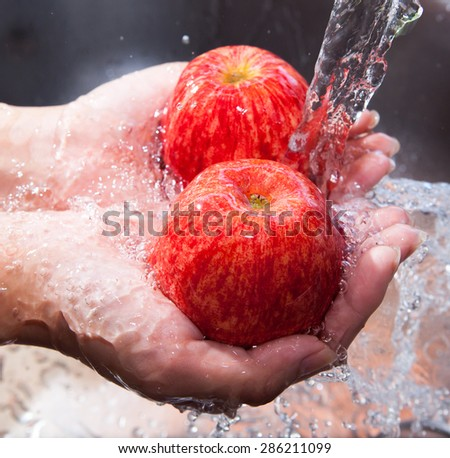 Red apple with water splash on hands, Fresh an Healthy foods concept