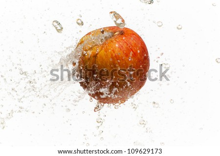 Red apple with water splashes on white background