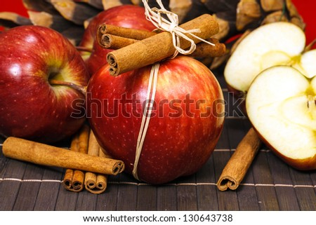 Red apples and cinnamon sticks. Red winter apples with cinnamon sticks
