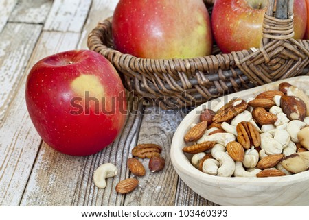red apples and nuts (cashew, walnut, almond, Brazilian) in rustic setting (primitive wooden bowl and wicker basket over grunge painted wood surface)