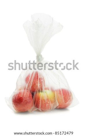 Red apples in translucent plastic bag on white background