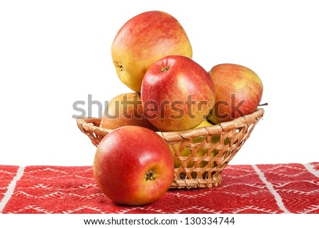 red apples in wicker basket on red tablecloth. country style