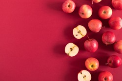 Red apples on a red background. Flat lay, top view, copy space