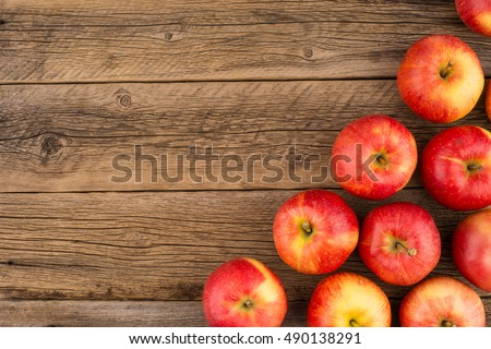 Red apples on the old wooden table. Top view.