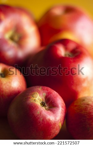 Red apples presented on wooden board.