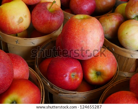 Red Apples sitting in a wooden basket at a farm market after being picked