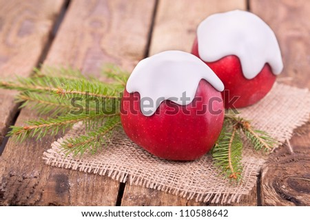 red apples with white icing, winter apples with green fir branches, Christmas time