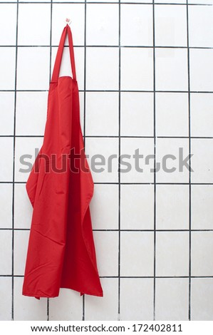 Red Apron Hangs On Wall.