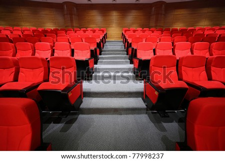 Red arm-chairs and gangway are in empty hall - stock photo