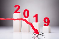 Red Arrow Cracking White Surface In Front Of Decreasing Year 2019 Graph