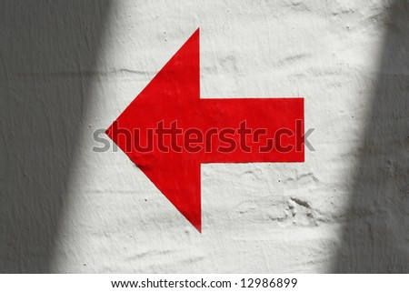 Red arrow on white wall with shadow