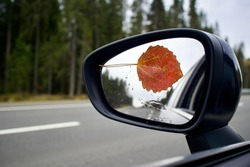 Red autumn leaf on the sideview, rearview mirror of a car on road with drops of rain