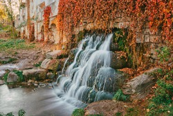 Red autumn leaves borders artificial waterfall through ruins of medieval castle wall.