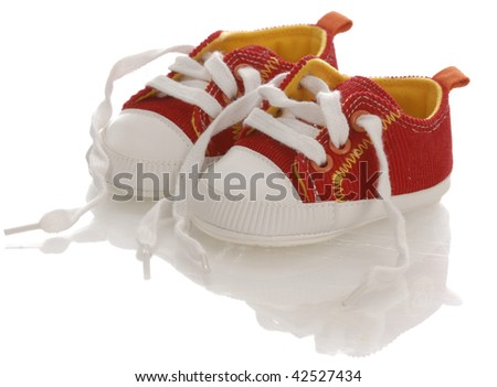 red baby on infant running shoes with laces untied