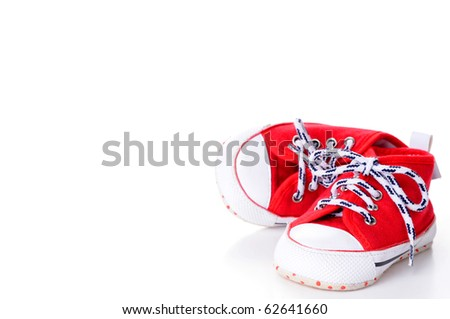 Red baby running shoes with ample copy space. - stock photo