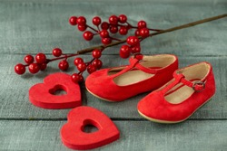 red baby shoes as decor and background on dark wood surface, Christmas decorations for newborns close-up