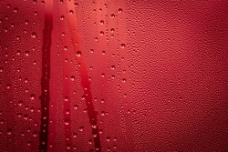 Red background - rain drops on a window glass