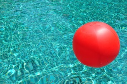 Red ball floating in a swimming pool.