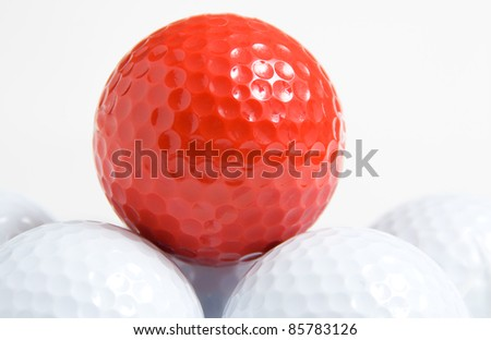 red ball of golf accompanied by white balls