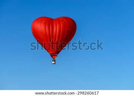 red balloon in the shape of a heart against the blue sky