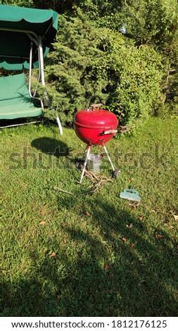 Red Barbeque on grass in garden Stok fotoğraf ©