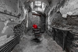 Red Barber chair in a run down prison cell in black and white