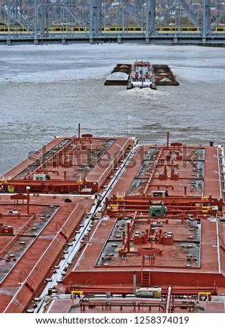 Red barge speeding to overtake and pass a smaller barge