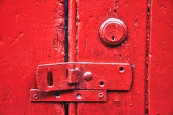 red barn door detail of lock and latch