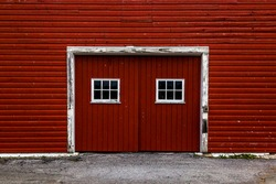 Red barn doors on a red barn with a white frame