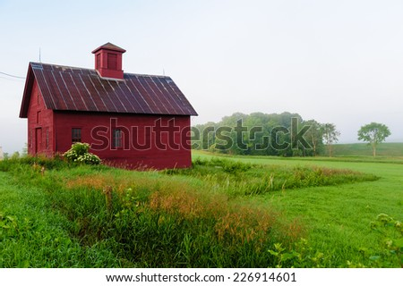 Red barn in the early morning mist, Stowe, Vermont, USA.