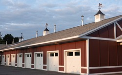 Red barn with white doors and cupolas and clouds