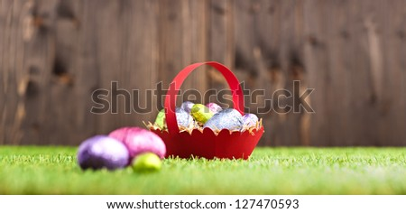 Red basket with Chocolate Easter eggs in an outdoor setting