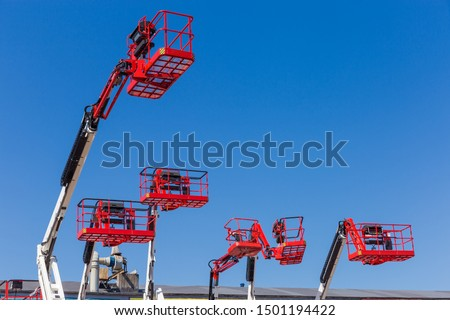 Red baskets on the white booms of different articulated boom lifts and top parts of lifts on a background of clear sky #1501194422