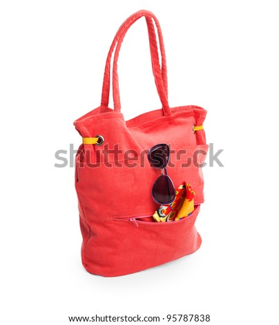 red beach bag with glasses and towel