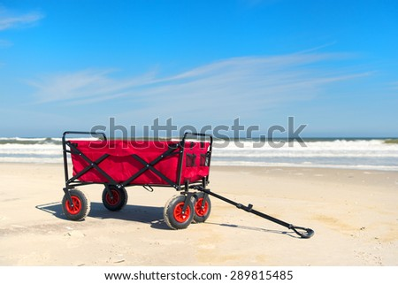 Red beach cart standing in front of sea