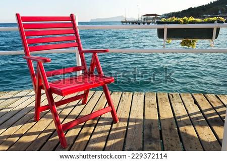 Red beach chair. Red beach chair on a pier over the sea