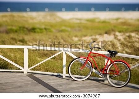 Red beach cruiser bicycle leaning against walkway rail on beach on Bald Head Island, North Carolina.