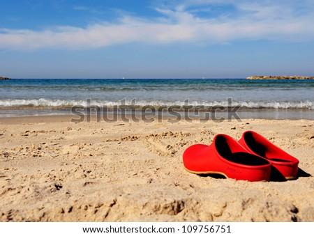 Red beach shoes left on the send in Tel-Aviv beach on the coastline of the Mediterranean sea. Israel.