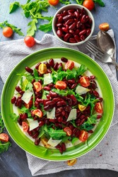 Red beans and wild rocket healthy salad with cherry tomatoes, sea salt flakes and parmesan shavings drizzled with olive oil
