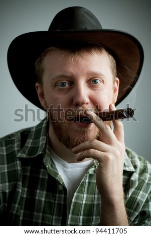 Red-bearded man in a cowboy hat and a shirt with a cigar in his mouth