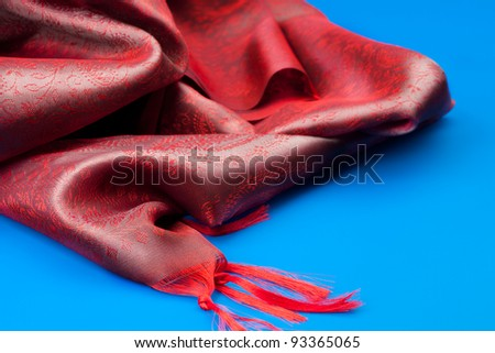 Red beautiful fabric on blue table with beautiful folds
