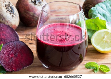 Red beet juice in a glass on a wooden background with lemon and beet greens