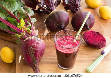 Red beet juice in a glass with whole fresh beets and lemons